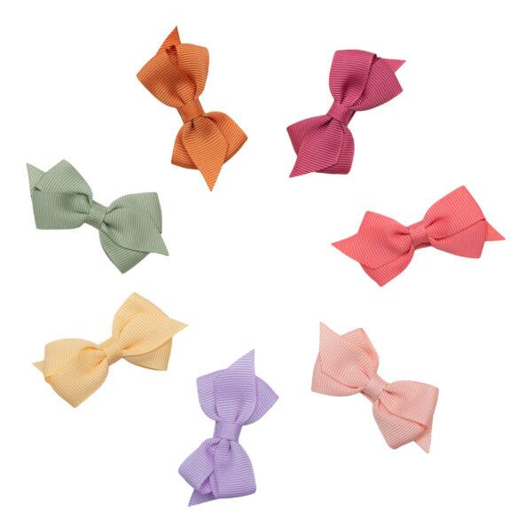 Sød lille sløjfe fra Little Wonders i dejlige lyse sommerfarver. Du kan derfor med sikkerhed finde en sløjfe der passer til netop det tøj som din prinsesse har i skabet. Denne sløjfe er lavet i 1,5 cm. bredt grosgrain bånd.